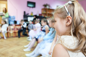 Small girl sitting in kindergarten class room at music lesson